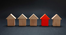Red House Model Among Wooden Houses, Black Color Background