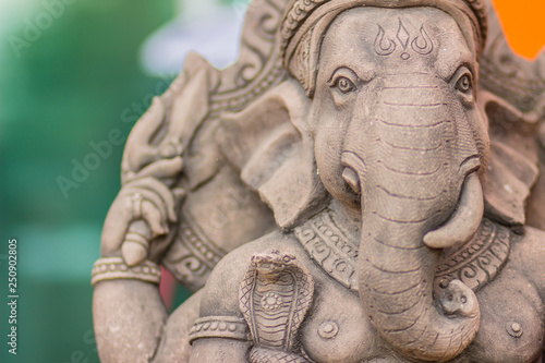 Photo  Gray stone statue of ganesha head with cobra at public park, also known as Ganapati, Vinayaka, Pillaiyar and Binayak, with his elephant head, big paunch, over which he ties a snake and a broken trunk