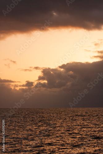 Sky, sunset, ocean, sea, water, ocean waves, clouds, glowing light, colorful, calming, vertical image
