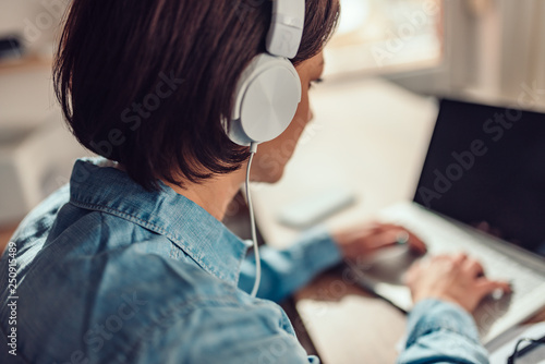 Woman using laptop and listening music on a headphones - 250915489
