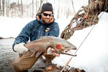 Fisherman Holding Large Steelhead Fish Frozen River Fly-fishing In Pulaski NY On The Salmon River. Fly-fishing For Steelhead/ Rainbow Trout.