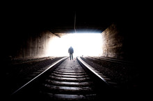Man On Railway. Young Man Going On Rails To The Bright Light In The End On A Tunnel