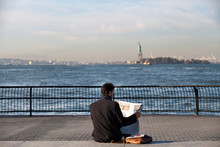 Mid-adult Man Reading Newspaper Statue Of Liberty In Background