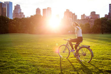 Young Woman Riding Bicycle In Central Park