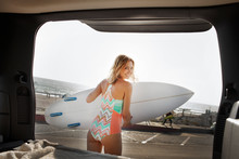 Smiley Young Woman Holding Surfboard Next To Car