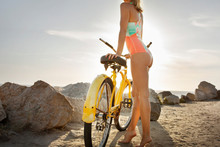 Young Woman In Swimming Costume Leaning On Bicycle On Beach