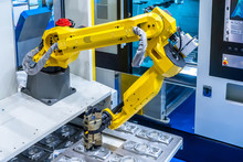 The Robot Arm. Manipulator Puts The Parts In The Machine..Robotic Technology. Automation Of Production. Industrial Work Of The Robot Manipulator. Robots In Production.