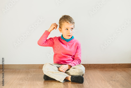 Fototapeta Independent child of 5 years combing himself sitting on the floor of his house obraz na płótnie