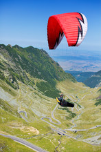 Man Parachuting Over Valley