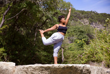 Young Woman Exercising On Rock