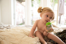 Little Girl (18-23 Months) Sitting On Bad And Drinking From Baby Bottle