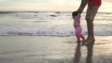 Portrait Of Little Girl Pulling Parents' Arms  Run To The Beach