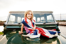 Girl (2-3) Wrapped Up In British Flag Sitting On Car Hood