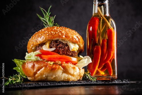 Fototapety, obrazy: American home cooking. a large grilled burger with pork cutlet, tomato, cucumber, with a fried sesame and razmarin roll. unhealthy food. copy space