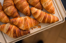 Many Large Croissants Are Placed On A Light Brown Tray.