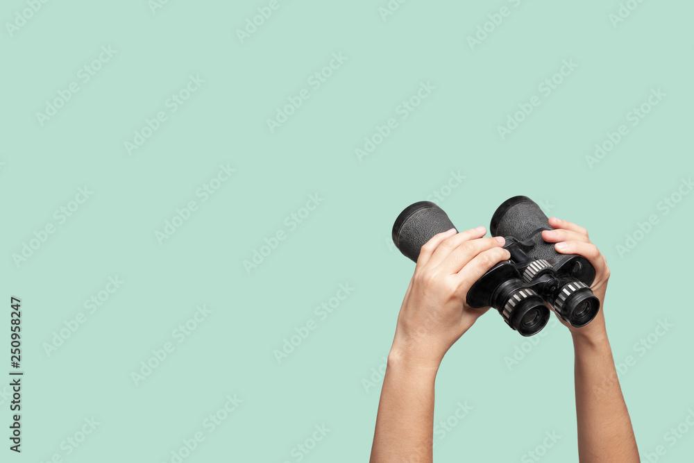 Fototapety, obrazy: Hands holding binoculars on green background