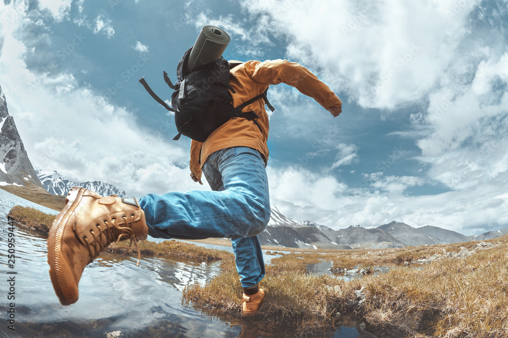 Obraz Man hiker jumps across water in mountain area fototapeta, plakat