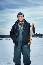 Portrait Of Fisherman Holding Dead Fish On Frozen Lake