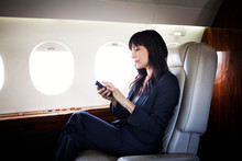 Woman On Smart Phone On Airplane