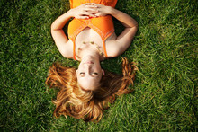 Young Woman With Blond Hair Lying On Grass