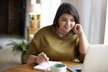 Modern Electronic Gadgets, Job And Occupation Concept. Cute Elegant Young Brunette Female With Excess Weight Using Laptop Computer For Remote Work, Looking At Screen, Holding Pen, Writing Down