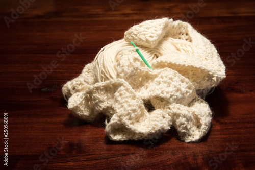 Fotografie, Obraz  White Alpaca Yarn Crochet Project With a Vintage Gteen Crochet Hook Laying On a