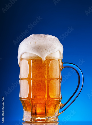Photo  Faceted mug of the light beer with foam on blue background