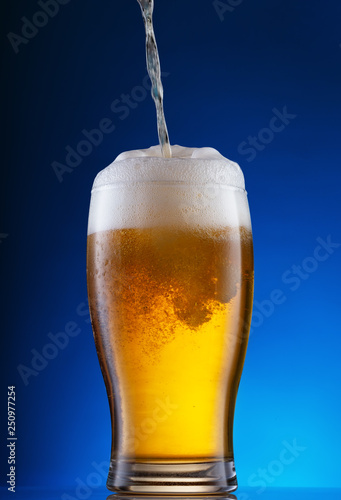 Photo  Light beer pouring into glass on blue background