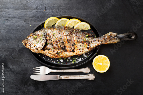 Fotografie, Obraz Tasty grilled fish dorado with  lemon on kitchen table.