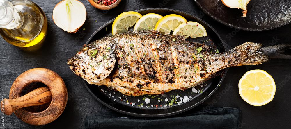 Fototapeta Tasty grilled fish dorado with  lemon on kitchen table.