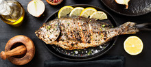 Tasty Grilled Fish Dorado With  Lemon On Kitchen Table.