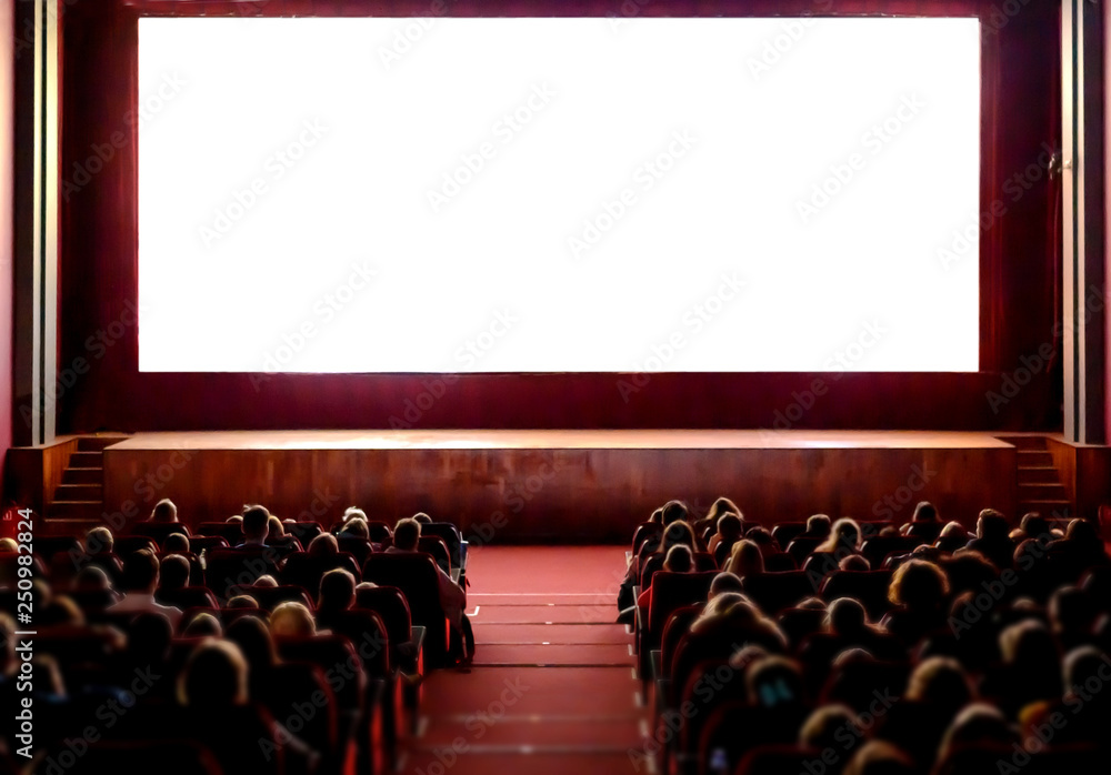 Fototapety, obrazy: People in the cinema auditorium with empty white screen.