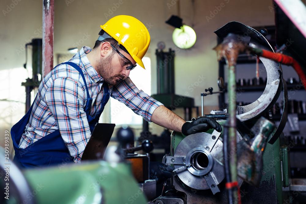 Fototapeta Metal worker turner operating lathe machine at industrial manufacturing factory