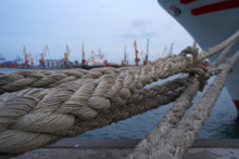 Lots Of Rope Knots Leading To Moored Ships. Boat Ropes, Ship. Mooring Post On The Waterfront , Element For Mooring Ships In The Harbor, Safety
