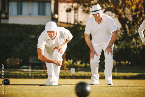 Photo  Old men playing a game of boules