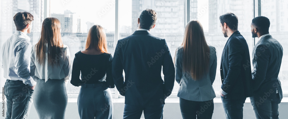 Fototapety, obrazy: Business colleagues looking through window, back view