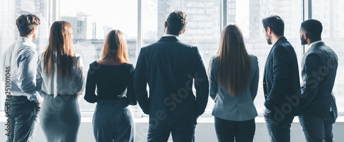 Photo  Business colleagues looking through window, back view