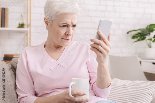 Senior woman with vision problems using phone Canvas Print