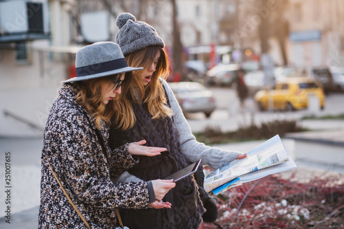 Stylish city portrait of two fashionable girls trying to