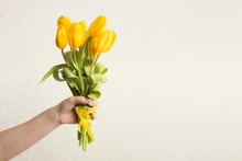 Hand Holding Bunch Of Tulips At White Background, Copy Space