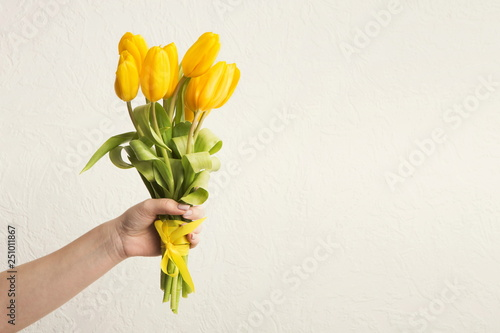 Photo  Hand holding bunch of tulips at white background, copy space