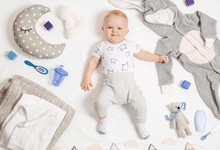Cute Little Baby With Clothing And Accessories On White Background, Top View