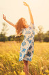 Beautiful young girl throws up his hands flowers field sunset