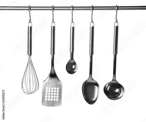 Fotografía  Set of kitchen utensils hanging against white background