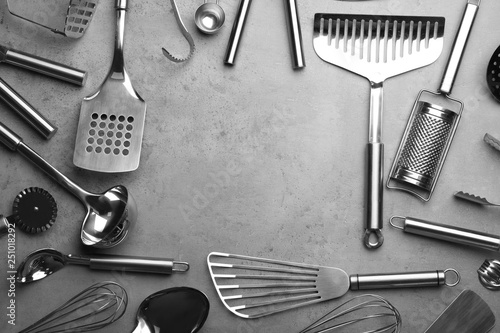 Fotografía  Flat lay composition with different kitchen utensils on grey background, space f