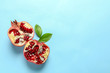 Leinwanddruck Bild - Ripe pomegranate halves on color background, top view with space for text