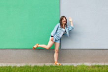 Full Length Portrait Of Happy Excited Beautiful Woman In Casual Jeans Denim Style In Summertime Standing Near Green And Light Blue Wall, Looking At Camera Greeting And Waving Her Hand