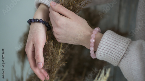 Fotografia bracelets of purple and pink stones on the hand, in the hands of dried flowers,