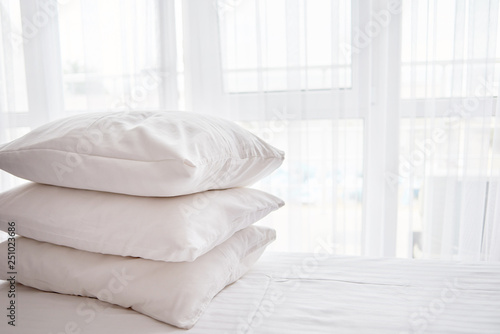 Fotografie, Obraz  Stack of white soft pillows on comfortable bed sheet with window on background,