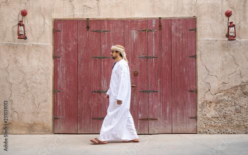 Fotografie, Obraz  Arab Man walking in old Al Seef area of Dubai